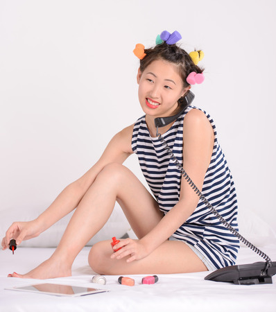 long toes: Portrait of Asian female sitting on bed at home. Talking on the phone and doing pedicure