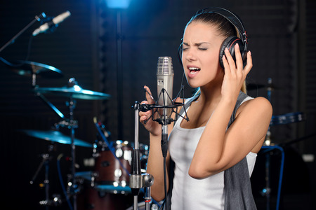 Portrait of young woman recording a song in a professional studio Stok Fotoğraf