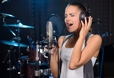 singing: Portrait of young woman recording a song in a professional studio Stock Photo