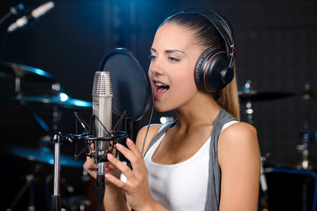 studio portrait: Portrait of young woman recording a song in a professional studio Stock Photo