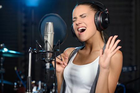 プロのスタジオで歌を録音する若い女性の肖像画 写真素材