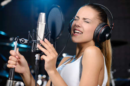 rock star: Portrait of young woman recording a song in a professional studio Stock Photo