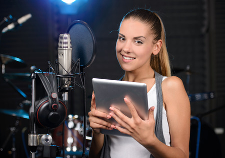 Portrait of young woman recording a song in a professional studio photo