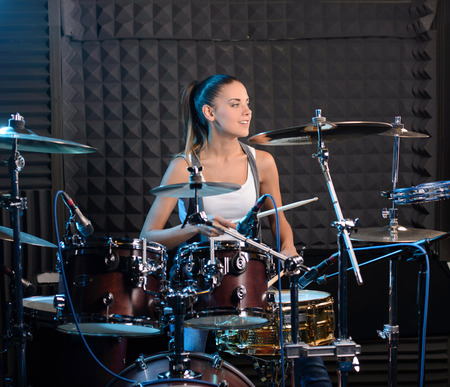 Girl behind drum-type installation in a professional recording studio photo