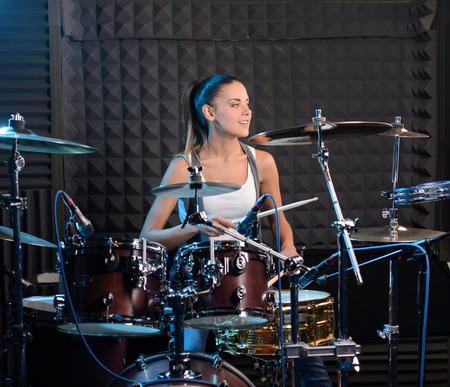 estudio de grabacion: Muchacha detr�s de la instalaci�n de tambor en un estudio de grabaci�n profesional