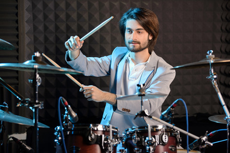 drumset: Young man behind drum-type installation in a professional recording studio