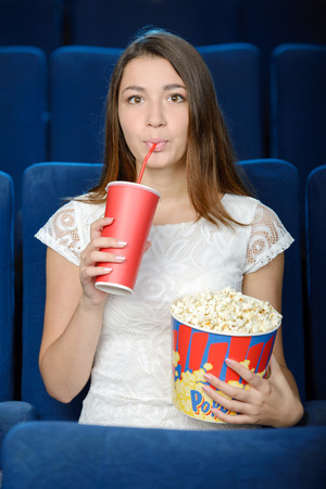 raised eyebrow: Women at the cinema. Beautiful young women eating popcorn while watching movie at the cinema