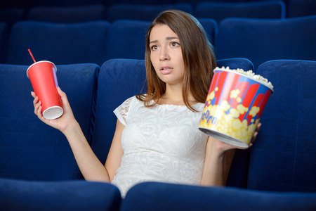 Women at the cinema. Beautiful young women eating popcorn while watching movie at the cinema photo