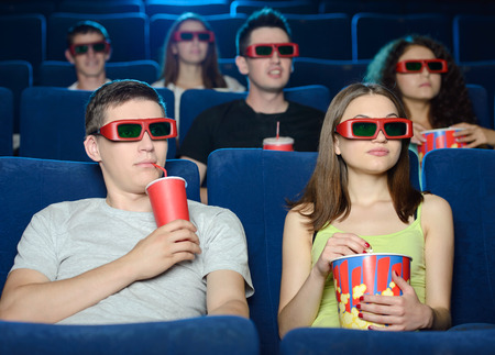 Exciting movie. Young people eating popcorn and drinking soda\ while watching movie at the cinema
