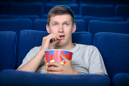 Men at the cinema. Excited young men watching movie at the cinema and eating popcorn photo