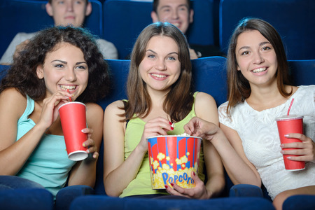 Exciting movie. Young people eating popcorn and drinking soda while watching movie at the cinema photo