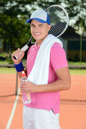 tiring: Tennis player posing in front of a tennis court