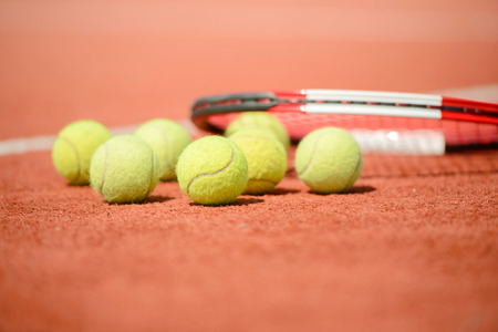 View of tennis racket and balls on the clay tennis court photo
