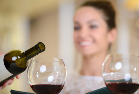 Young elegant woman waiting for a glass of wine while sitting in a restaurant photo