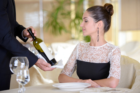 Young elegant man waiter serve wine for a young elegant woman in a restaurant photo