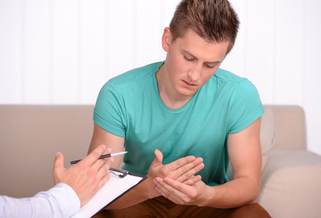 Een jonge man vertelt over zijn problemen met zijn psycholoog Stockfoto - 30273504