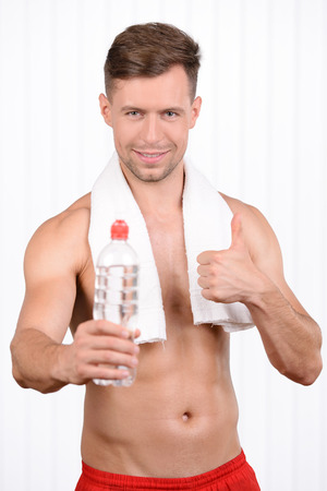 refreshed: Get refreshed! Cheerful young muscular man holding a bottle with water in his hand and smiling Stock Photo