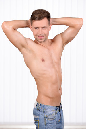 Keeping his body in good shape. Cheerful young muscular man demonstration of his body photo
