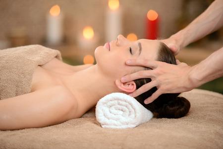 massaggio: Ritratto di fresca e bella donna bruna prendendo massaggio alla testa isolato su sfondo spa salon