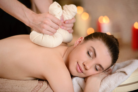 Smiling woman getting a back massage with herbal compresses in the health spa Stock Photo