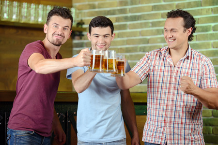 Friends cheering. Three happy soccer fans drinking beer at the pub photo
