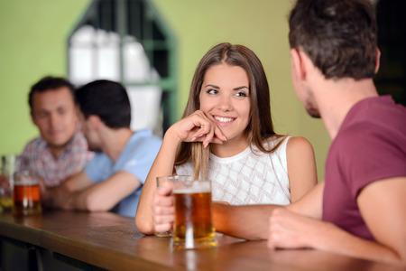 Beer lovers. Young cheerful couple drinking beer at the bar photo