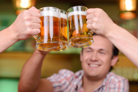 Close-up of young gay men to hold glasses of beer in a beer pub