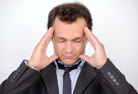Feeling headache. Portrait of young man in formalwear holding head in hands and keeping eyes closed while standing against grey background photo