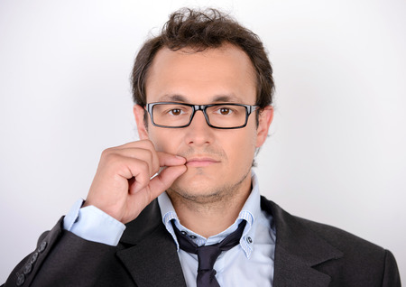 I will say nothing. Portrait of young man in formalwear closing his mouth by hand while standing against grey background