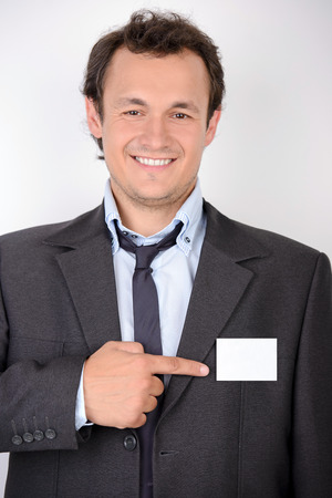 Young and bossy man in formalwear looking at camera and pointing his badge while standing against grey background photo