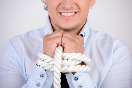 Tied up businessman. Frustrated young businessman with tied up hands looking away while standing against grey background photo