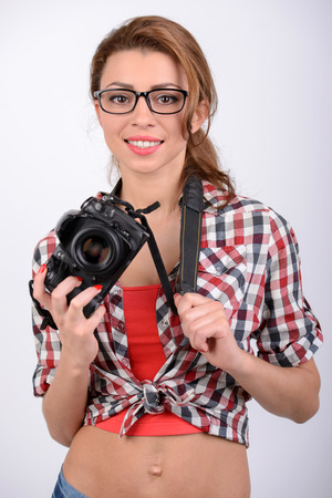 composing: Attractive brunette aims her camera. composing a photograph in studio, isolated on white Stock Photo