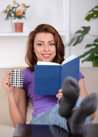feet on desk: Young girl sitting on couch and reading a book Stock Photo