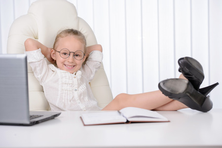 Little business woman. Cute girl with glasses and a solemn sitting at a desk and using laptop, resting legs on table. Big shoes