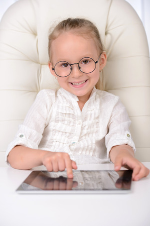 easier: Making business easier. Cheerful little girl in glasses and formalwear sitting at the table and working on digital tablet Stock Photo