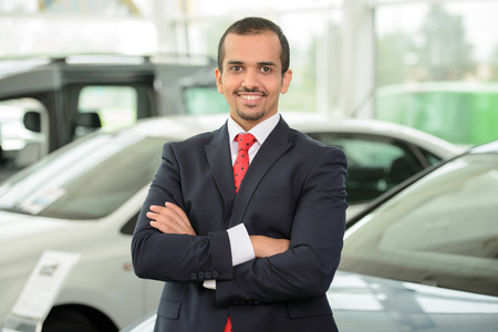 Confident man in formalwear leaning at the car and looking at camera while standing at car dealership Stock Photo