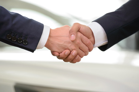 car dealership: Good deal. Close-up shoot of the hands shaking in front of the car