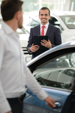 Handsome young classic car salesman standing in the dealership and helping a client to make a decision photo