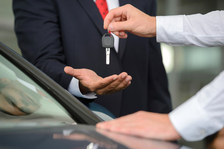 Giving a key of a brand new car. Handsome young classic car\ salesman giving a car key to the owner and smiling