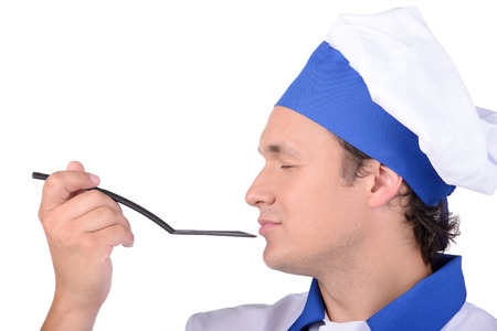 delightfully: Male cook delightfully smelling the contents of  spoon