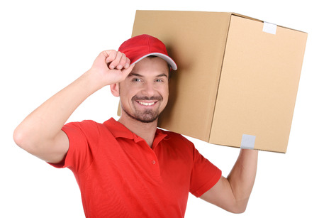 Happy smiling delivery man carrying boxes isolated on white background Foto de archivo