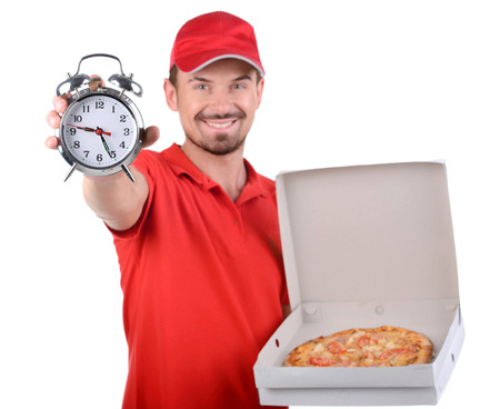 eating pizza: Cheerful young deliveryman holding a pizza box while isolated on white