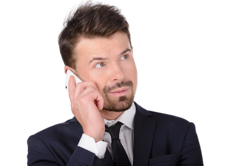 Angry businessman with mobile phone. Furious young businessman holding a mobile phone and pointing it while isolated on white photo