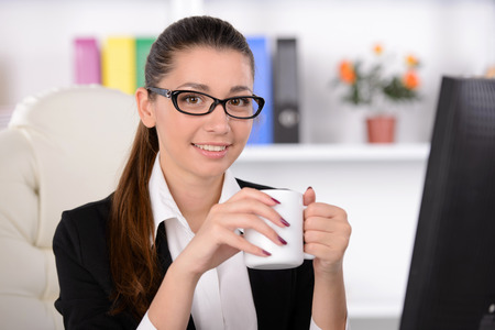 working place: Businesswoman drinking coffee. Confident business woman sitting at her working place and drinking coffee Stock Photo