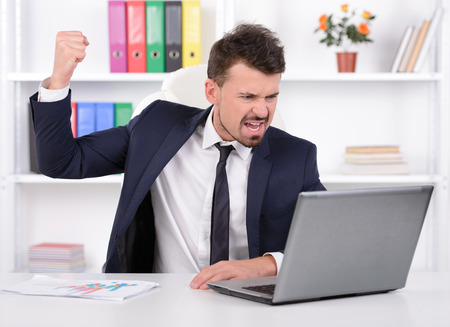 working place: Furious young businessman gesturing while sitting at his working place