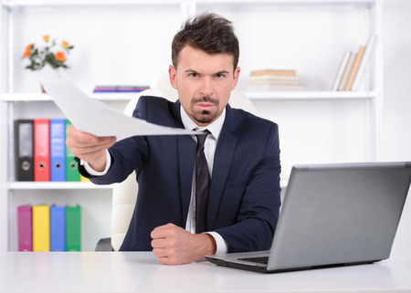 Furious young businessman gesturing while sitting at his working place photo