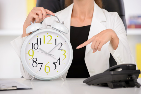 rushing hour: Attractive businesswoman showing white clock in office