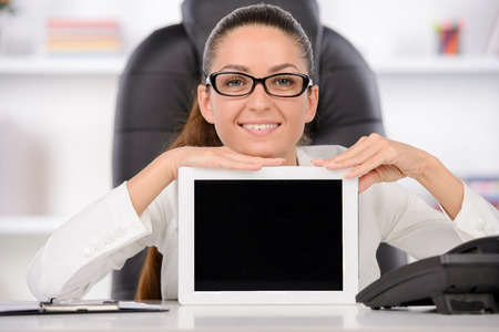 Happy business woman in her office presenting a tablet computer photo