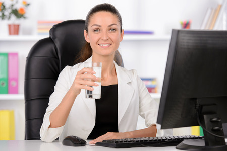 Pretty caucasian businesswoman reading and drinking water. photo