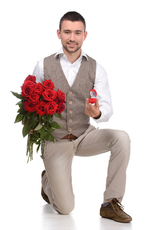 Will you marry me? Young man in full suit standing on one knee and making a proposal while isolated on white background photo